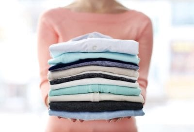 woman with a stack of folded laundry