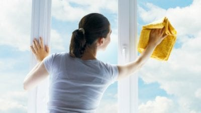 Girl washing windows on a move out clean