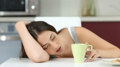 Woman asleep at table with coffee, reached burnout