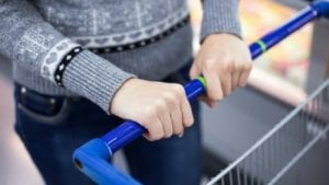 Hands with no gloves on shopping cart handle