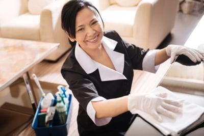 maid cleaning while wearing disposable gloves