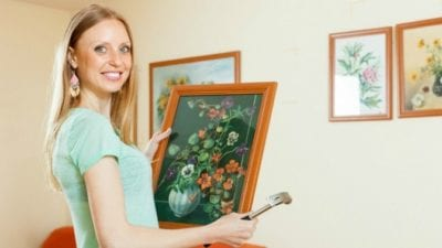 Handyman jobs house cleaners can do - woman hanging pictures