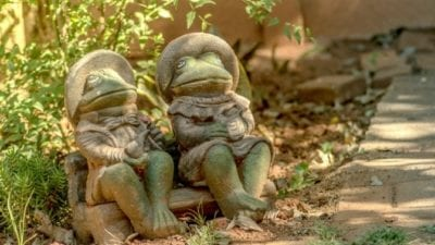 grief hoarding frog couple sitting on bench garden statues