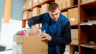 Organizing man with box in warehouse