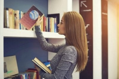 Hoarding Woman puts books on shelf