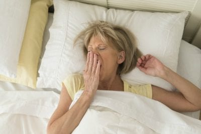 Menopause and House Cleaning, Woman Yawning in Bed