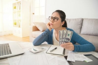 One-Offs, Woman Thinking at Her Desk While Holding Money