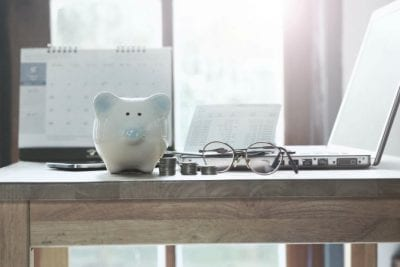 Annual Cost of Cleaning Supplies, Calendar, Piggy Bank and Laptop on Desk
