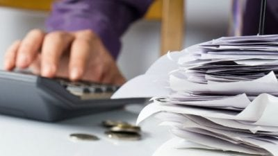Tax Tips Closeup of Hands entering receipts