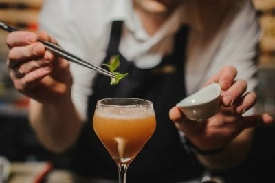 Upsell to Party Hosting from House Cleaning, Bartender Garnishing Drink