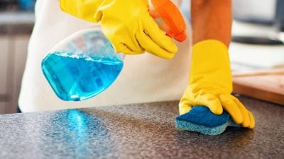 Clean or Paint First woman cleaning counters with sponge