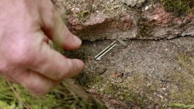 House Keys hand getting key from under rock