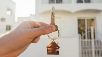 House Keys hand holding keys in front of house