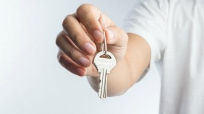 House Keys person holding out house keys