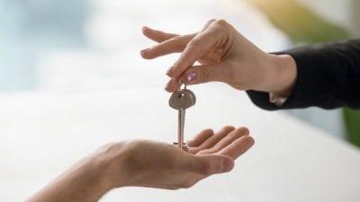 House Keys woman giving person house keys, closeup