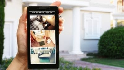 House Keys woman holding phone with home security camera feeds