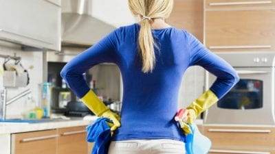Suspend House Cleaning Service housecleaner in kitchen holding cleaning supplies