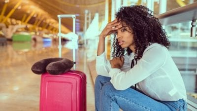 Guest Room Clean-Up stressed young woman sitting in airport, stranded