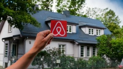 Guest Room man holding airbnb logo in front of house