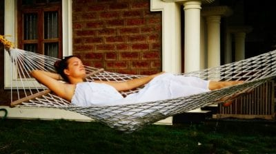 Airbnb Guests Clean Up, Woman Relaxing in Hammock