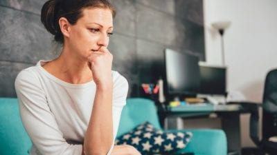 Botched Referral sad woman sitting on couch