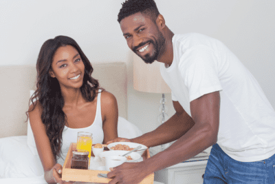 In Business With Your Spouse, Man Serving Breakfast in Bed to Woman