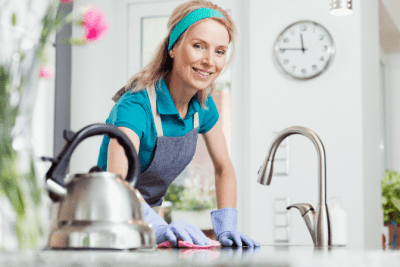 How to Get Your Cleaning Mojo Back, Happy Woman Cleaning Kitchen