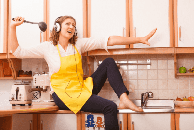 How to Get Your Cleaning Mojo Back, Woman in Kitchen Listening to Music