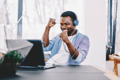 Start a Cleaning Company in Another Country, Excited Man Wearing Headphones Looking at Laptop