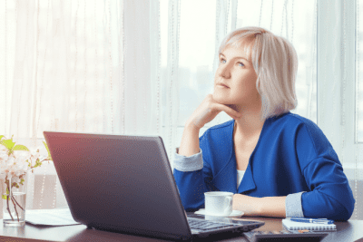 Start a Cleaning Company in Another Country, Woman Thinking and on Computer