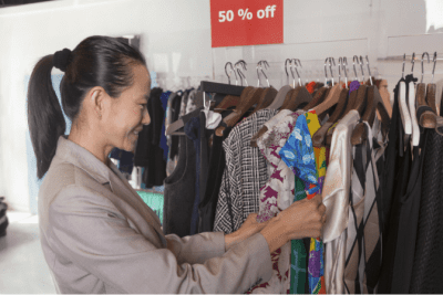 Can't Clean Because of Too Much Stuff, Woman Looking at Rack of Clothes