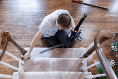 How to Clean Stairs, Man Vacuuming Stairs