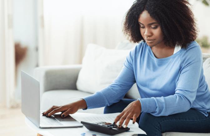 Becoming a Boss, Woman Using Calculator While at Computer