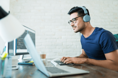 How Soon Can I Hire, Man Wears Headphones Types on Computer