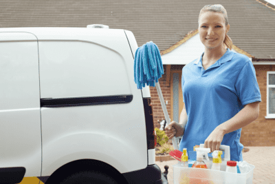 Brick and Mortar, Woman With Cleaning Supplies Outside House
